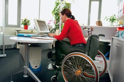 A képen egy megváltozott munkaképességű ember dolgozik egy íróasztalnál