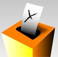 a képen egy szavazatokat gyűjtő láda látható, amint egy lap esik bele éppen a tetején lévő nyílásba