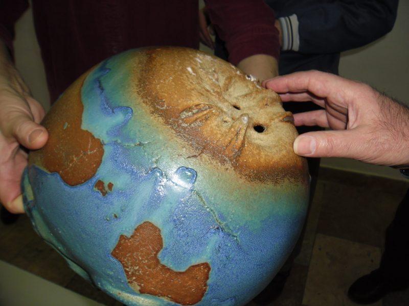 Egy földgömbszerű kerámia látható a képen, melyet valaki a kezével vizsgál