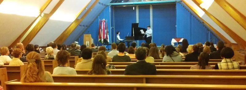 A klubtagok a színpadteremben hallgatják a zongoraelőadást