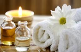 A képen egy illatgyertya, egy üveg masszázsolaj és egy virág látható, illusztrálva azt, hogy a masszázs a felfrissülés helye és ideje