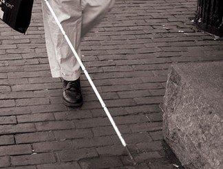 A képen egy láb látható, a láb előtt egy fehér bot