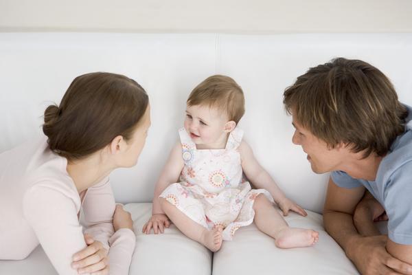 Egy gyermek ül az ágyon, a szülők meg mosolyogva figyelik őt
