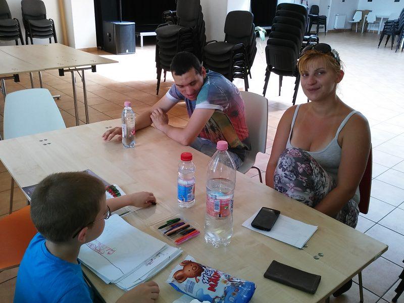 A képeken a klub tagjai láthatók, amint egy asztal körül ülnek