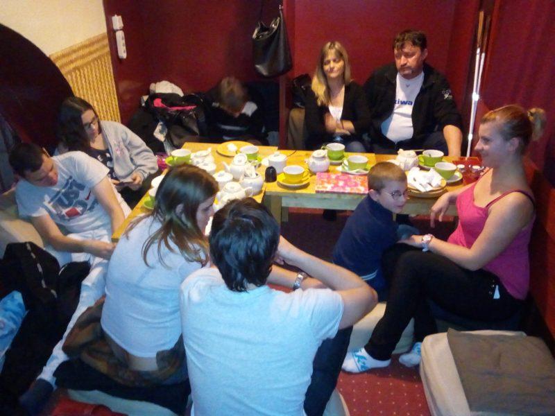 Az egyik teaházi teremben ülnek a tagok az asztal körül