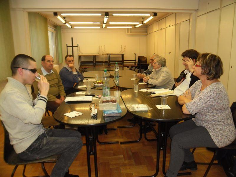 A klubtagok egy asztal körül ülve hallgatják Emőke előadását