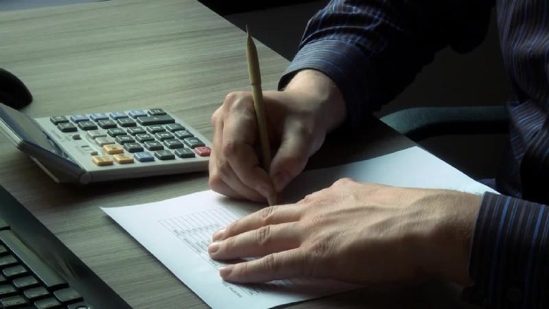 a képen egy ember számológépen számol és közben jegyzetel
