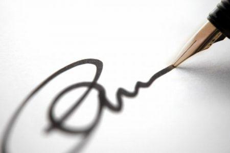 A képen egy toll látható, amint aláír vele valaki