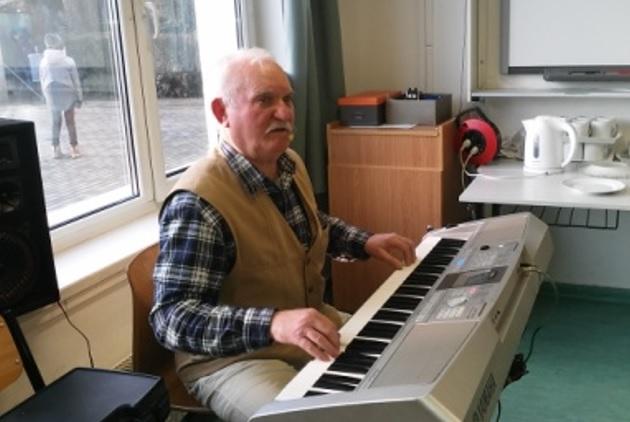 A képen Józsi bácsi látható a szintetizátorral, amint mindent elénekel, eljátszik nekünk, amit csak kérünk