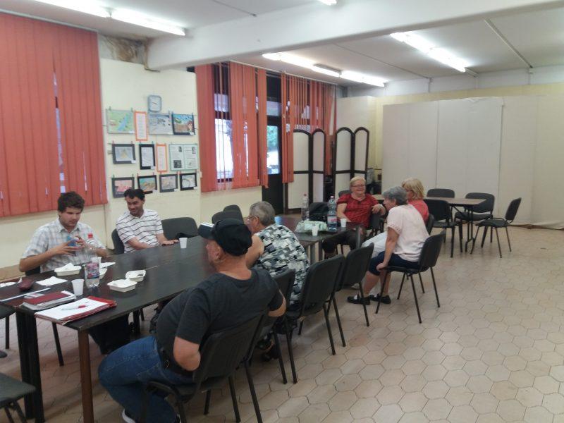 A képen egy asztal látható, mely körül a tagok ülnek és beszélgetnek