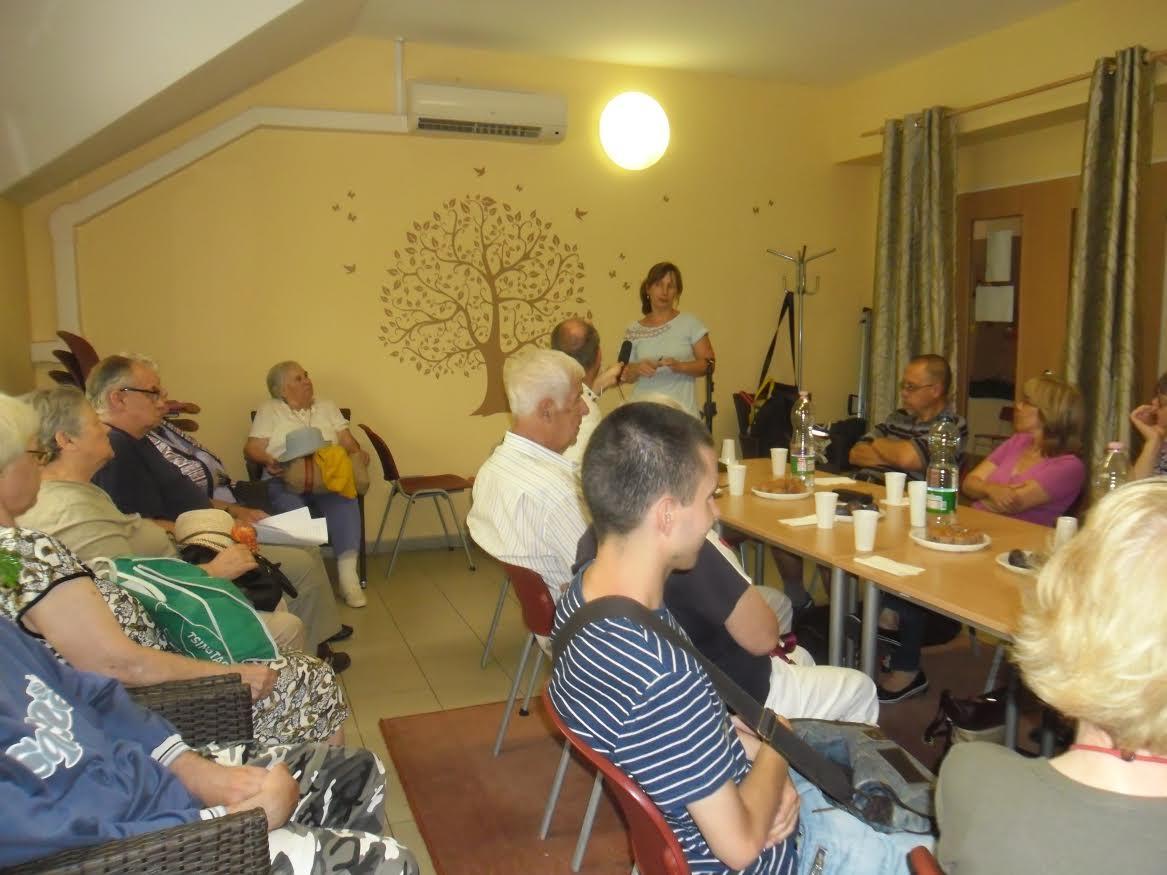 az előadás egy pillanata látható a képen, amint a klubtagok hallgatják a hallásvizsgáló hölgy ismertetőjét
