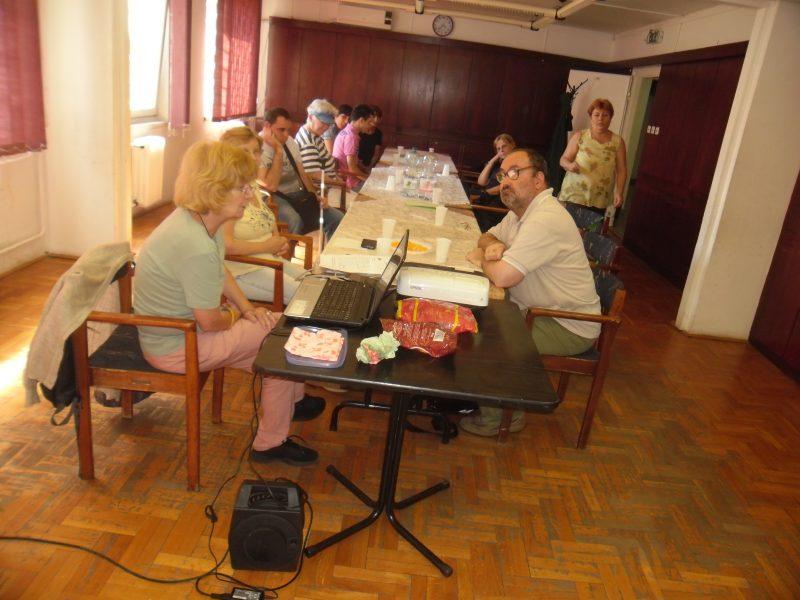 A képen az látható, amint az asztal körül ülve a klubtagok egy hangszórón keresztül verset hallgatnak