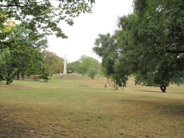 A képen a Tabán egy részlete látható, a zöld domboldallal és a hatalmas fákkal
