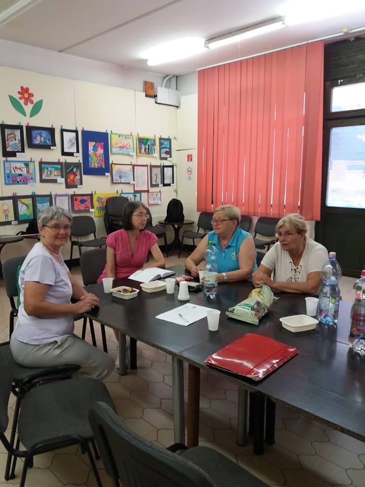 A képen a klubnap egy pillanata látható, mosolygó emberek ülnek az asztalnál