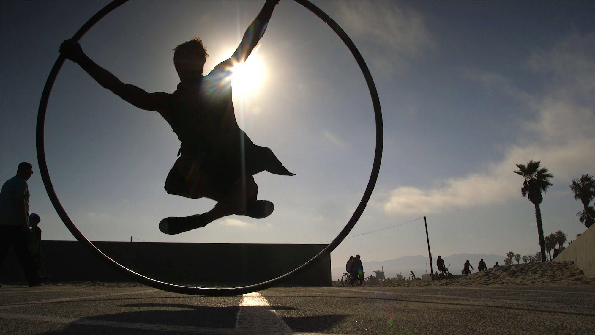 A képen a táncos körvonalait látjuk a lenyugvó nap fényében, ahogy megpördíti a karikát, miközben töröküléses pozíciót felvéve lóg benne, lírai fotó.