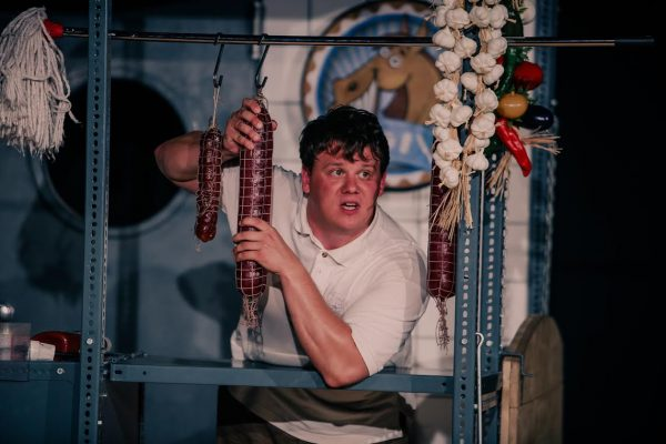 A képen a Csemegepultos naplója című darab egy pillanata látható, amint a csemegepultban álló ember, a színész, elmondja a közönségnek az élményeit