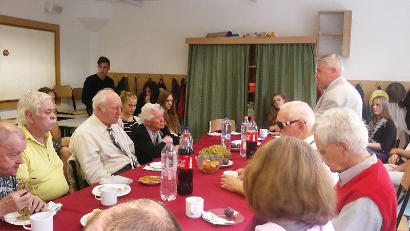 A képen a tagok ülve figyelik az előadót