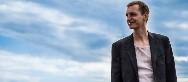 A képen: a film főhőse látható, kék éggel a háttérben. A fiatal férfi arcán hegek, viselt pólóján foltok éktelenkednek. Szájából egy cigaretta csonkja lóg ki. A férfi a távolba nézve mosolyog.