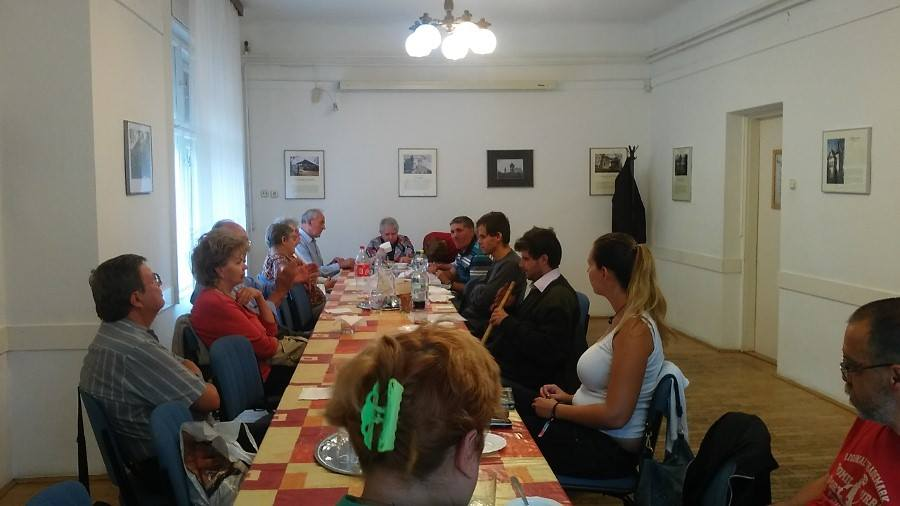 A képen a klubhelység látható egy hosszú asztallal, körülötte a tagok és a vendégünk