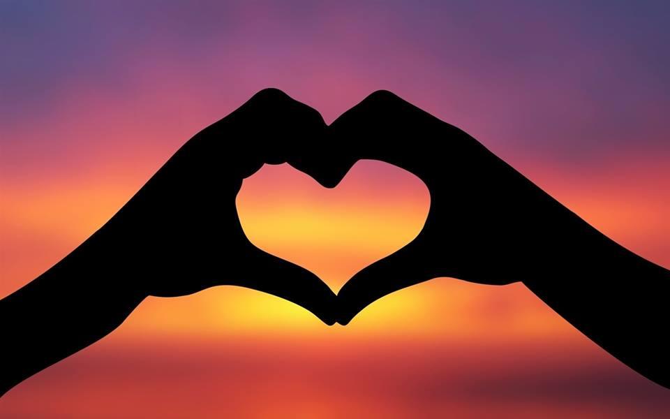Két kéz tűnik fel a természet által narancsos, lilás árnyalatokkal selymesen megfestett naplementében. A kezekre árnyék vetül, csak fekete sziluettjüket látjuk a színes háttér előtt. Egymáshoz illesztve, az ívesre hajlított ujjak egy tökéletes szívet formáznak.