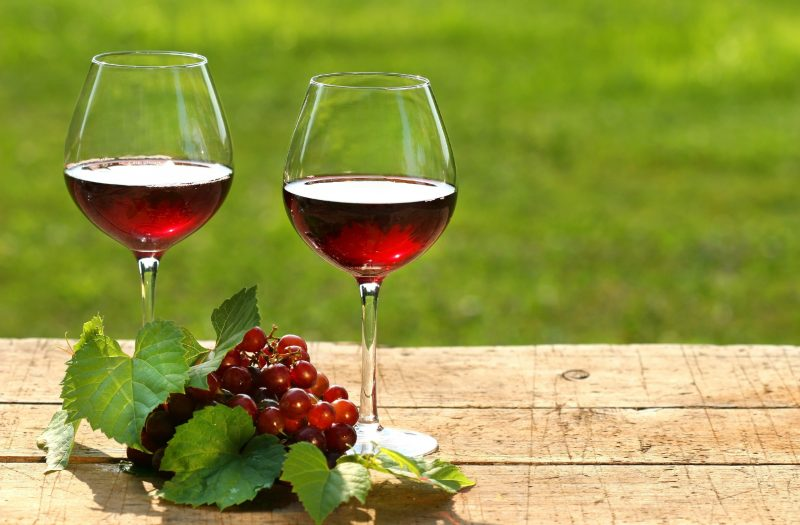 A képen két pohár vörösbor látható, egy fürt szőlővel, egy fából készült asztalon