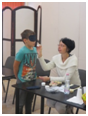 A képen Era látható érzékenyítés közben, amint illatokat mutat egy diáknak