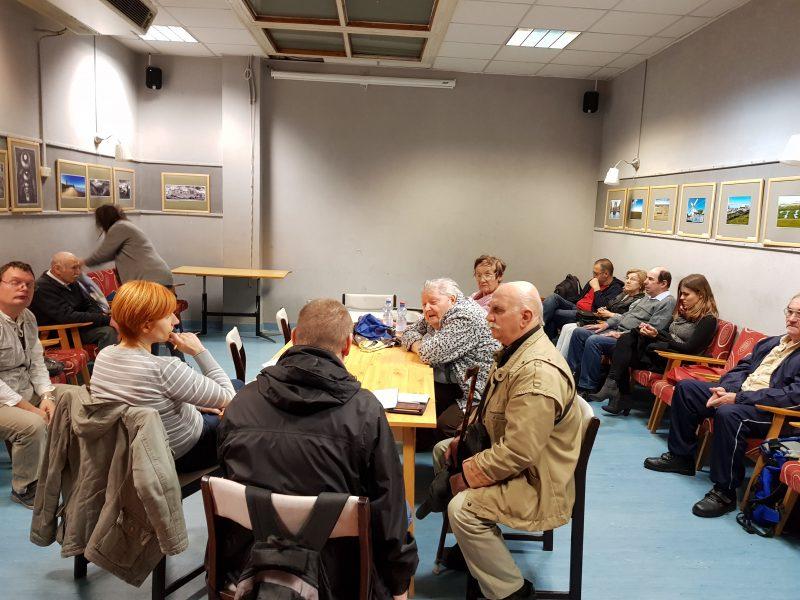 A képen nagyjából 14 ember van a teremben és hallgatják az ügyfélszolgálat munkatársait