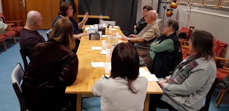 A kőbányai klubon a tagok beszélgetnek egymással egy asztal köré ülve