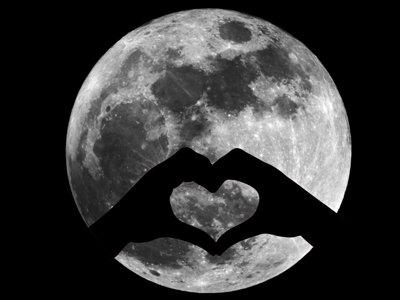 A Hold sápadt-szürke kráteres arcát látjuk a sötét égen. Előtte két kéz árnyéka, az összeillesztett ujjak egy szívet formáznak.