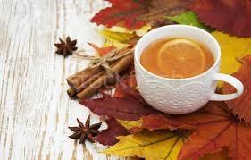 A képen egy bögre tea látható őszi faleveleken