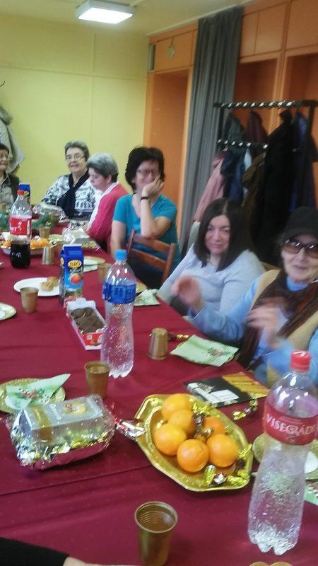 A klubtagok a gazdagon megterített asztal mellett ülnek