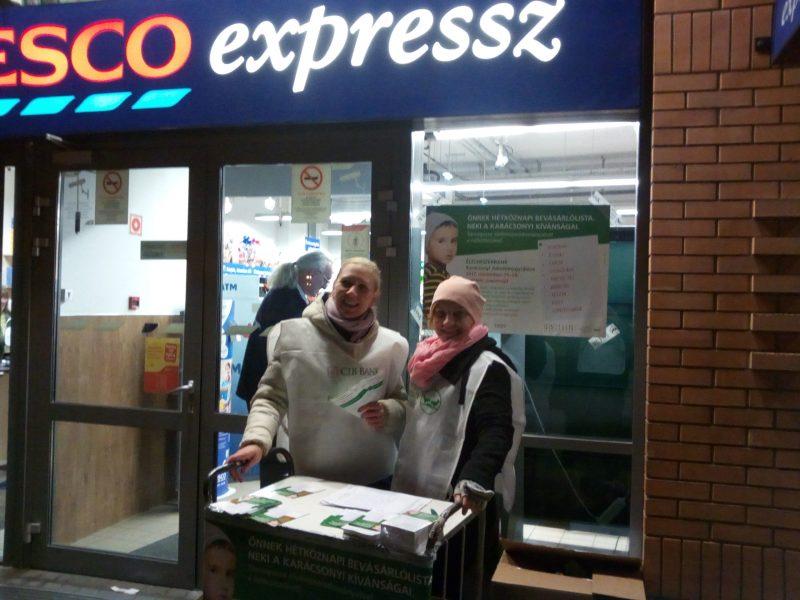 A képen a gyűjtés pillanata látható, két alkalmazottunk áll a bolt előtt