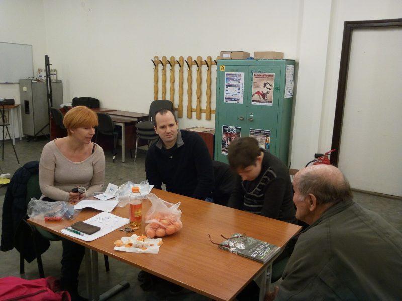 Az ügyfélszolgálat munkatársai egy asztal mellett ülve kérdésekre válaszolnak