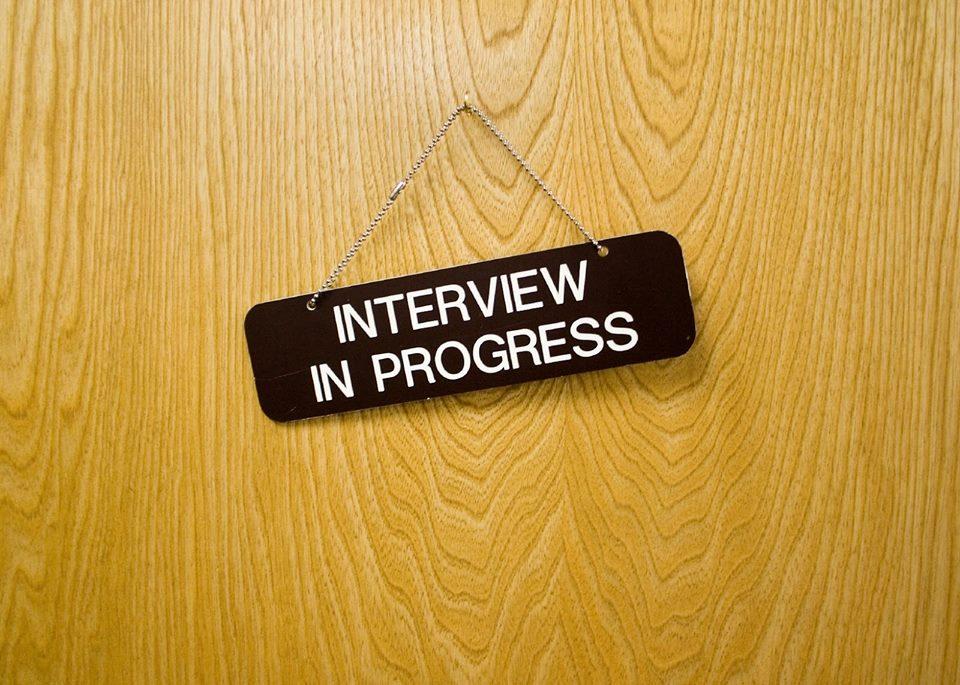 """A képen az """"Interview in progress"""", azaz """"interjú folyamatban"""" tábla látható egy faajtóra vagy burkolati elemre akasztva."""