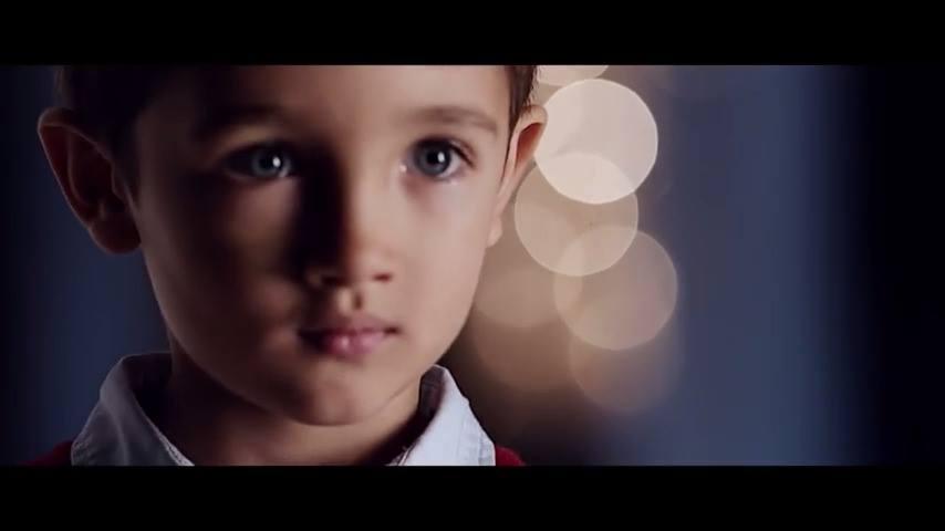 A csatolt képen a kisfiú arca látható, kicsit szomorkás, tiszta, őszinte, a háttérben elmosódó fényfoltok tűnnek fel.