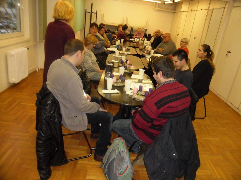 A képen a tagok a klubnapon az asztal körül ülnek