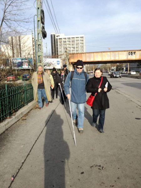 A képen a fehérbotos tesztelőkből és a szervezőkből álló sétacsoport tagjai láthatóak a Thököly úton, Zugló vasútállomásnál