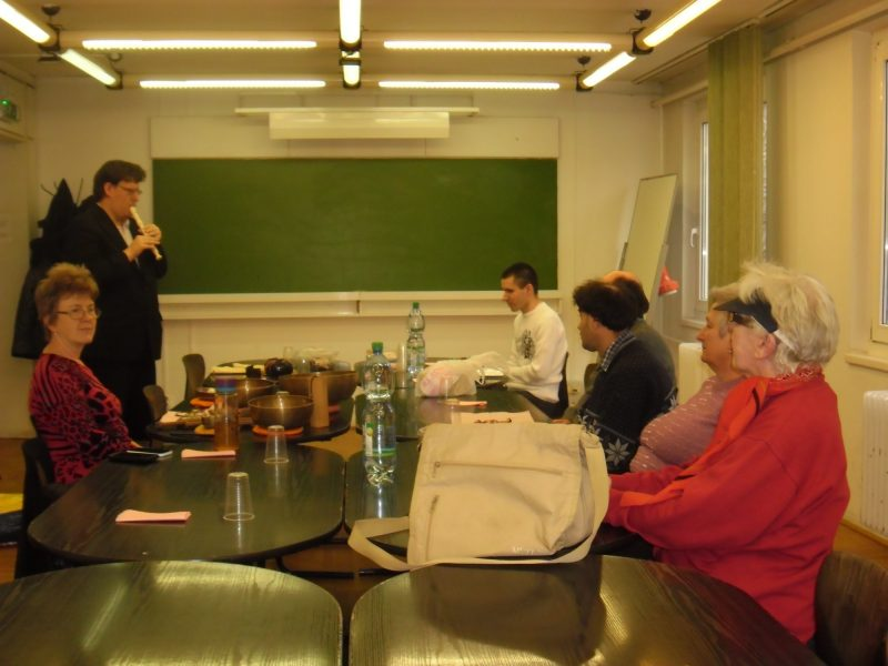 A képen az egyik klubtag furulyázik, a többiek asztal mellett ülve hallgatják