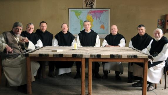 A képen a film egy plakátja látható, amelyen a szerzetesek egy asztal körül ülve vidáman néznek a kamera felé