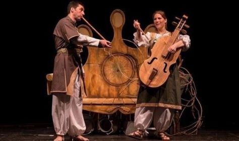 A képen az előadás egy részlete látható, ahol egy női és egy férfi szereplő zenél
