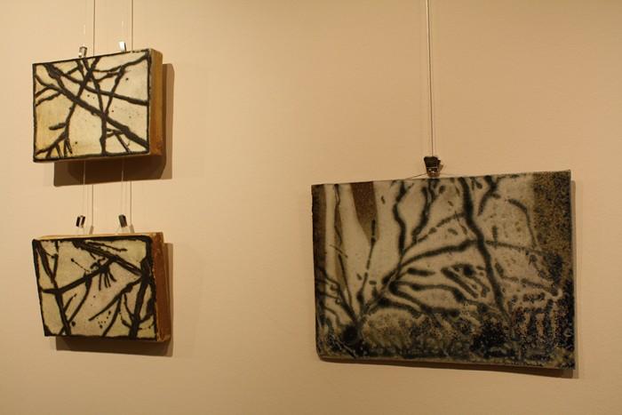 A képen a keramikus három alkotása látható, melyeknek a címe: egysorosok. A képeken egy kerámialapra festett faágak láthatóak