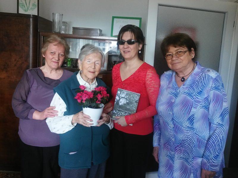 A képen Margitka néni látható, balján Terike, a kerületi közösségszervező, jobbján Fodor Ágnes a VGYKE elnöke és mellette Ádámné Szladovits Valéria