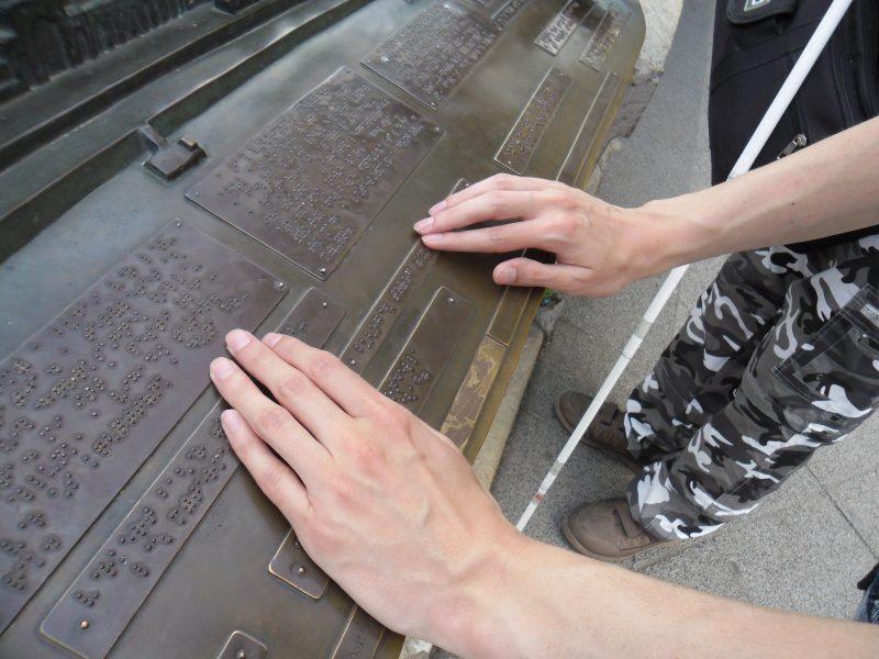 A korzó egyik Braille-felirata látható a képen amit a kispesti klub programján olvasnak ki a sétálók