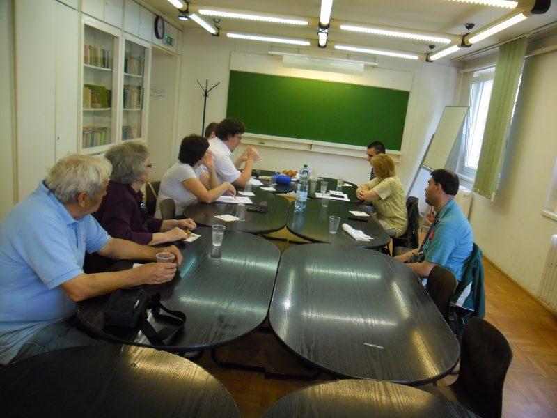 A 18. kerületi klub tagjai hat összetolt asztal mellett ülve beszélgetnek