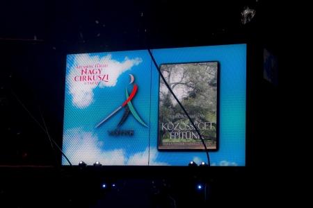 A fénykép a nagycirkusz könyvbemutatóján készült, a manézsban lévő hatalmas kivetítő látható, rajta a cirkusz nevével, a VGYKE logójával és a könyv címlapjával