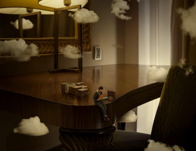 A képen egy ember látható, aki egy asztalnál ülve elmerül a versek olvasásában és e miatt összezsugorodik körülötte a világ