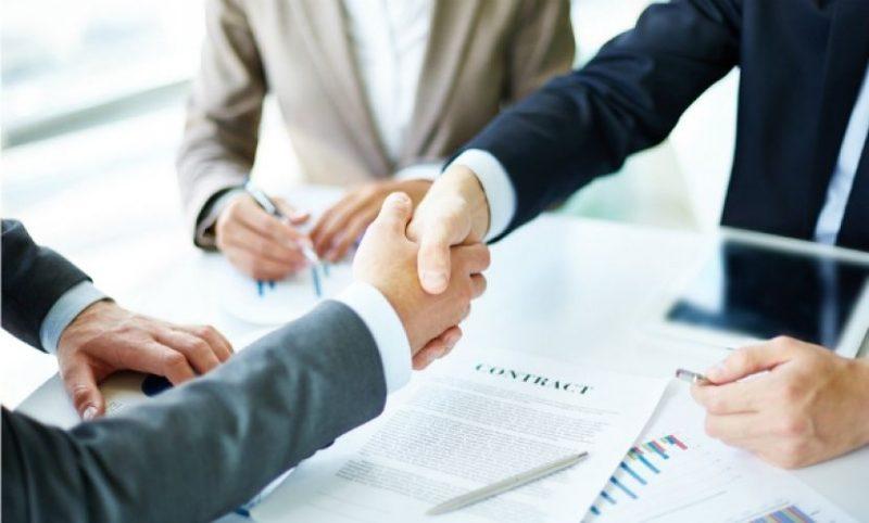 A képen az látható, amint két ember kezet fog egy szerződés aláírásakor, egy harmadik pedig mellettük ül