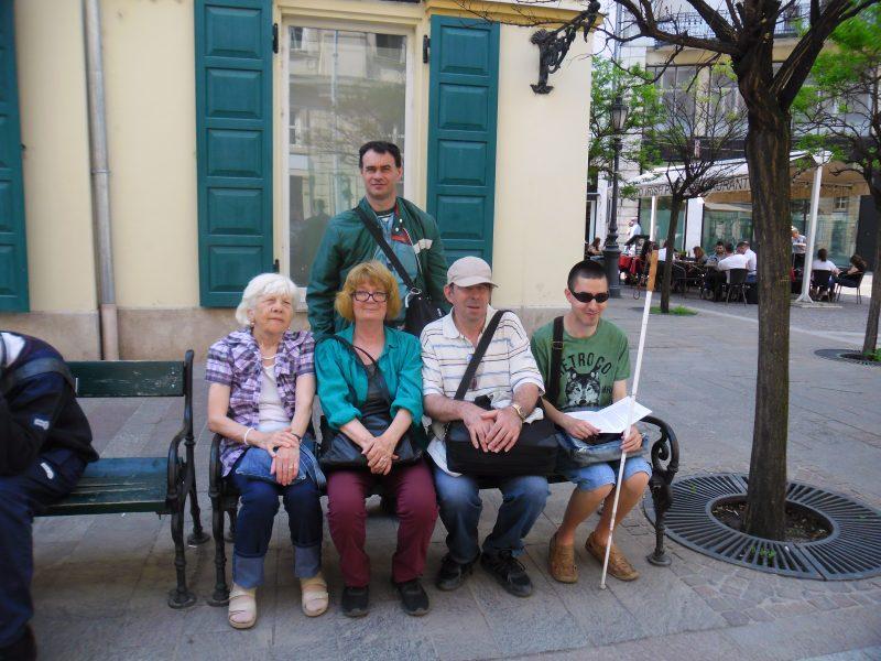 A séta résztvevői ülnek egy belvárosi padon