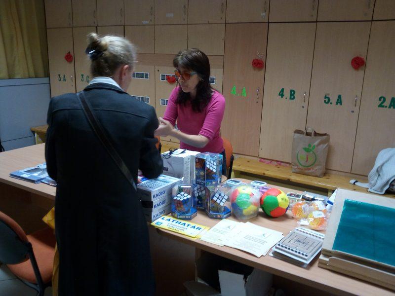 Egy szülő a Láthatár Bolt asztalánál beszélget a Gyengénlátók Iskolájában a kerületi szervezőnkkel