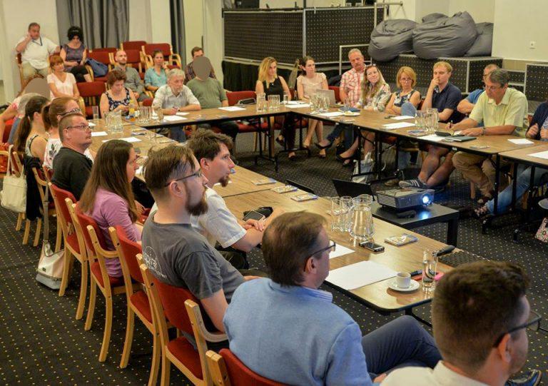 A képen a találkozó résztvevői láthatóak amint egy teremben ülve az előadásokat hallgatják